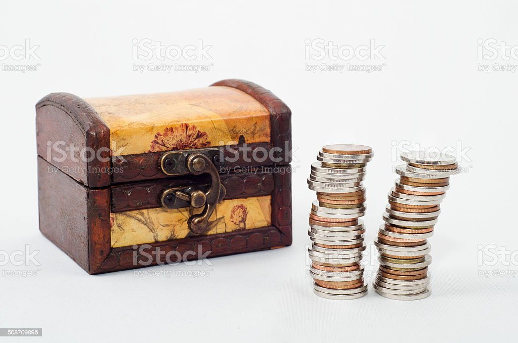 Wood chest and piles of coins stock photo