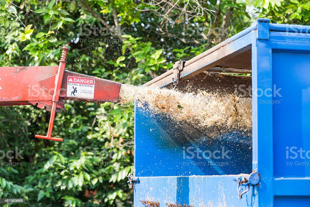 Wood chipper machine releasing shredded woods into truck stock photo