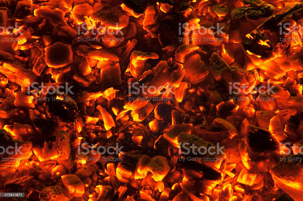 Wood embers burning background, close-up stock photo
