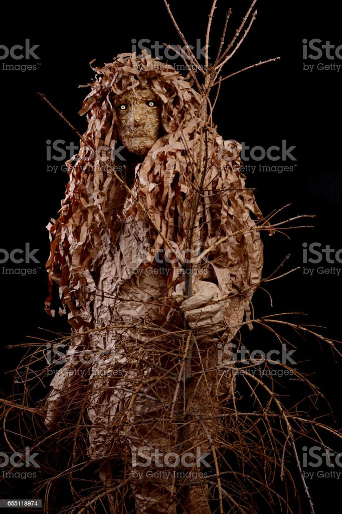 wood goblin with a tree in hands on a black background stock photo