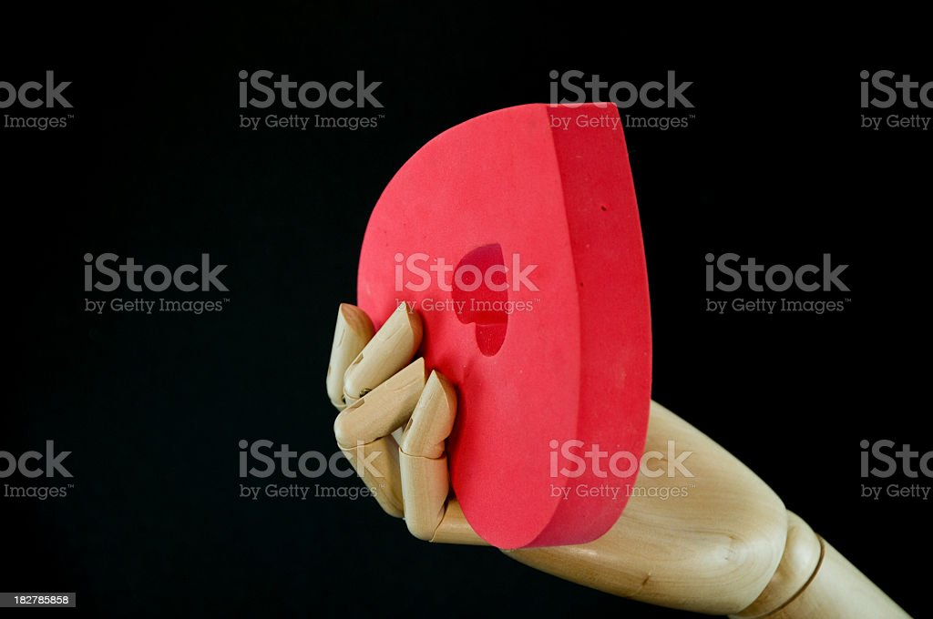 Wood hand and red foam heart on a black background royalty-free stock photo