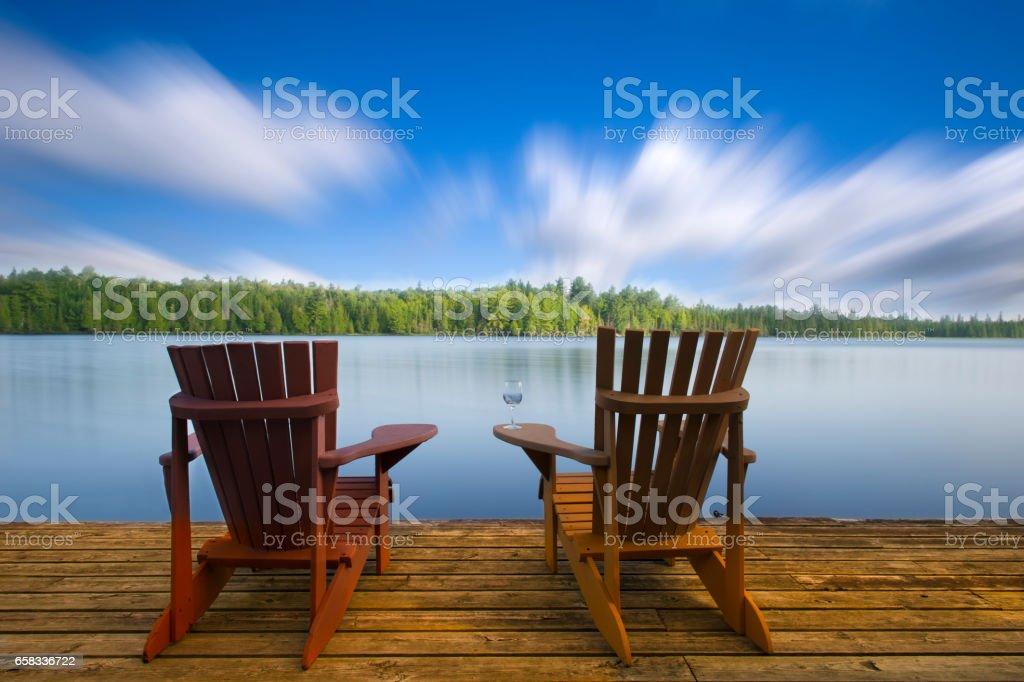 Wood Muskoka chairs on a lake deck stock photo