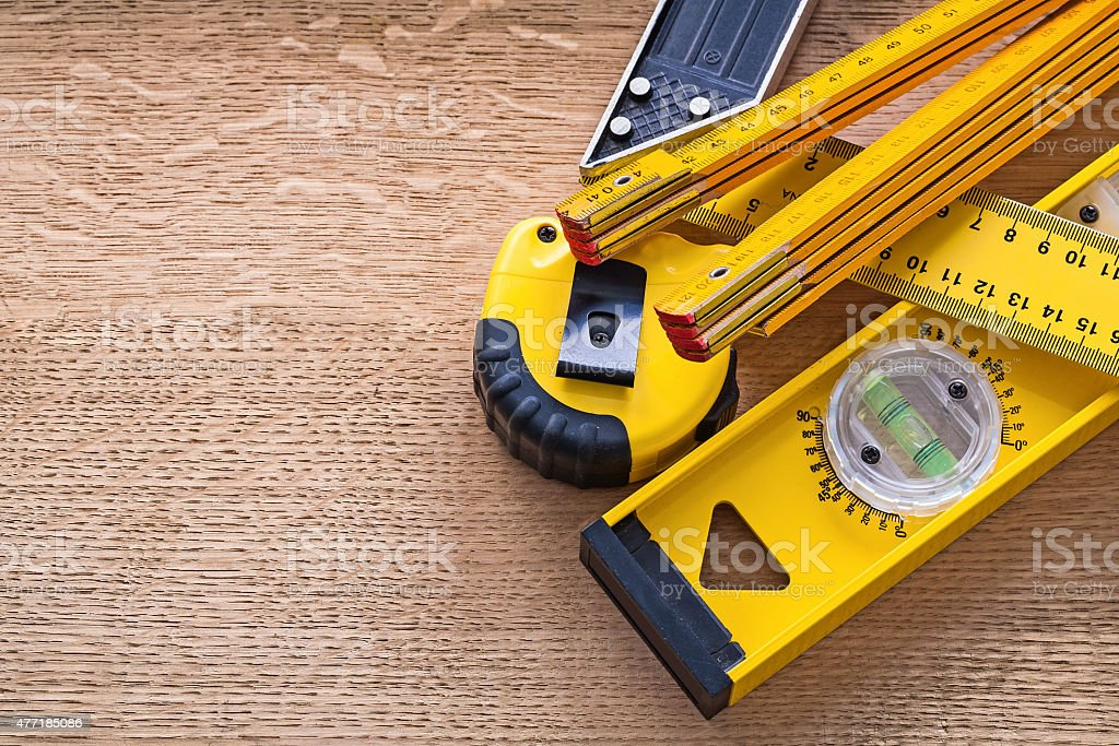 Wood oaken board with yellow objects of measurement construction stock photo