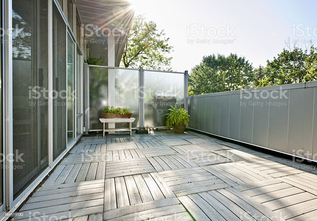A wood paneled floor on an apartment balcony with plants stock photo