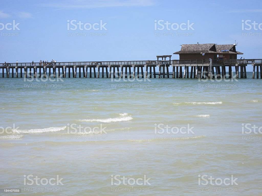 wood pier by beach in Naples Florida stock photo
