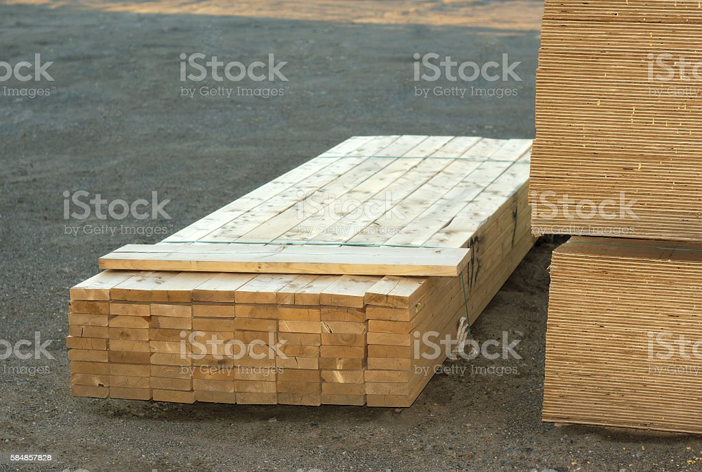 wood planks stacked on construction site stock photo
