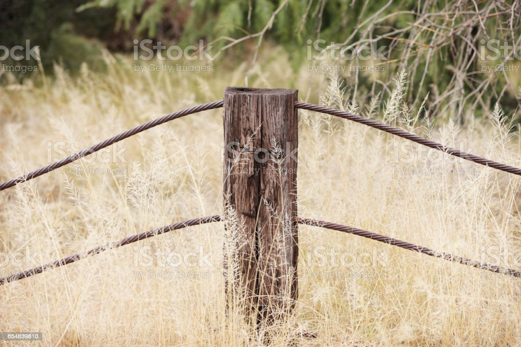 Wood Post Rusted Steel Cable Grassy Meadow stock photo