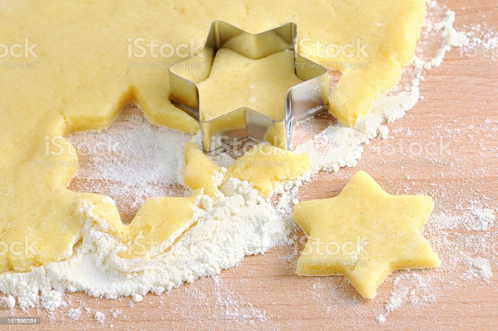 wood rolling pin and star shape pasty cutter on dough stock photo