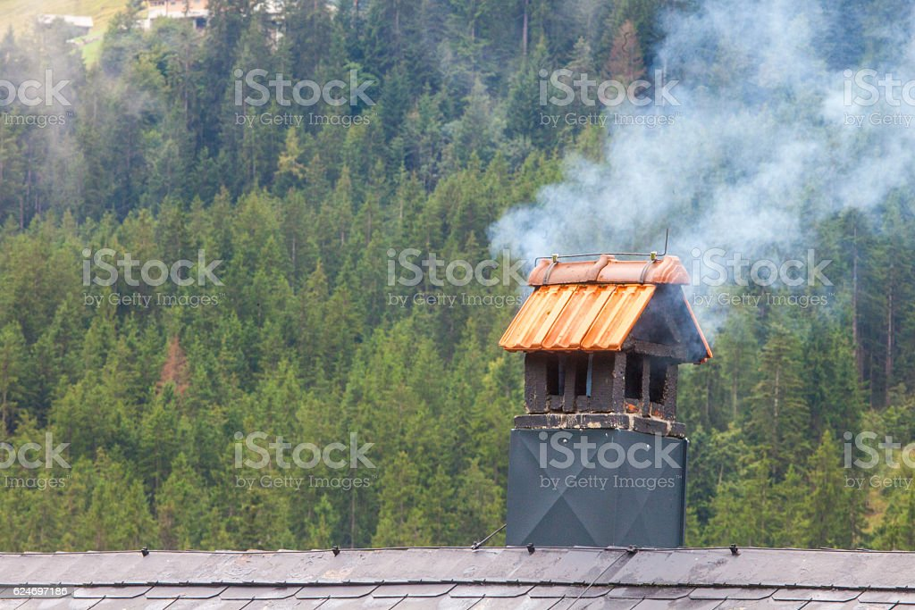 Wood smoke issuing from a chimney in Switzerland stock photo