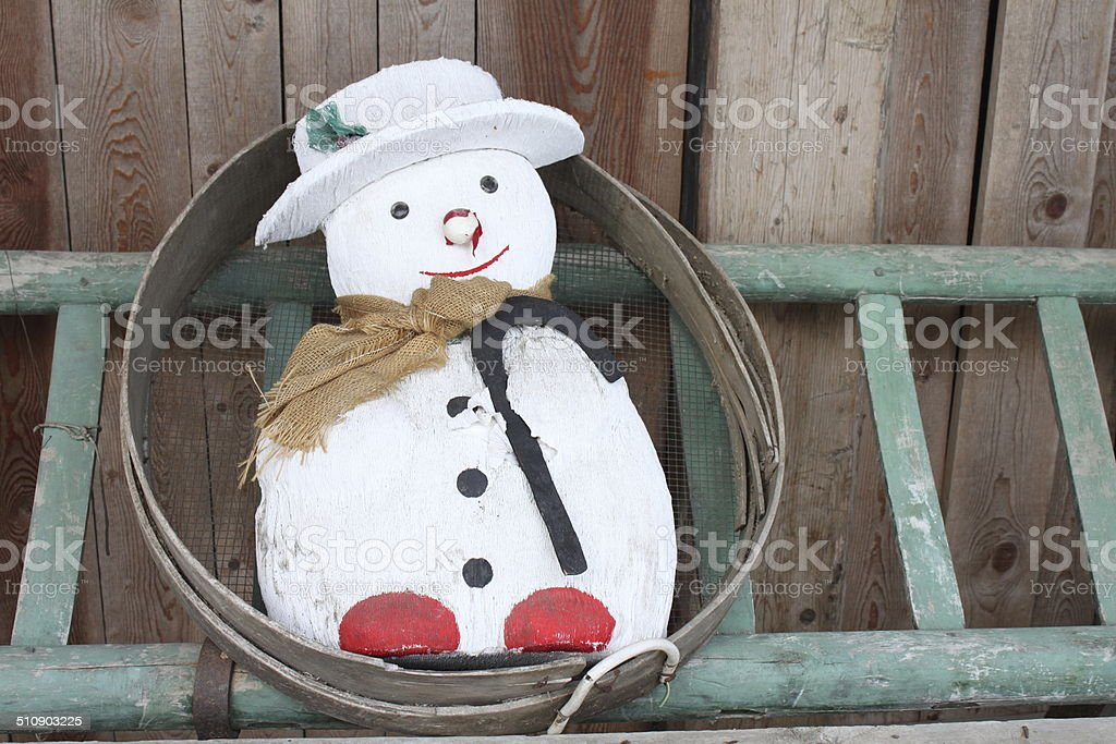 Wood snowman on a ladder royalty-free stock photo