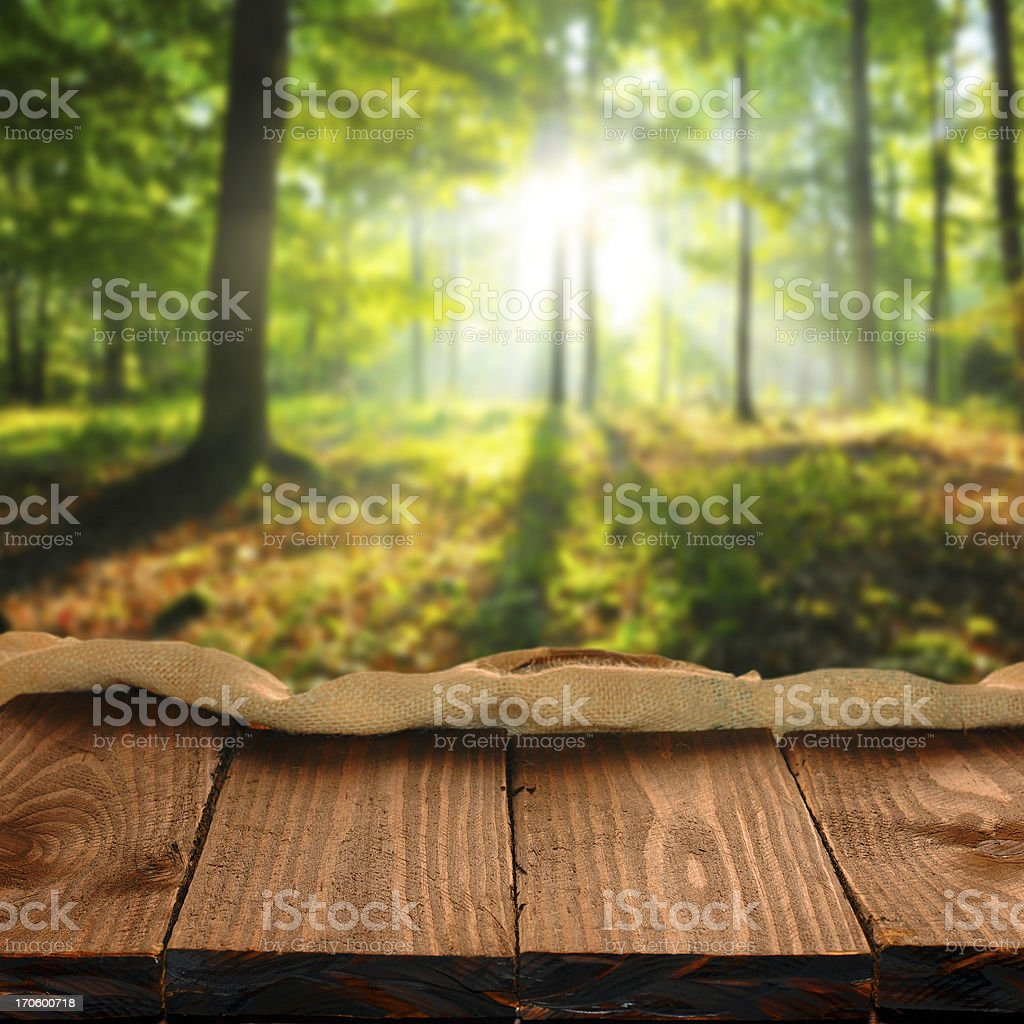 Wood table in foreground with light streaming through trees stock photo