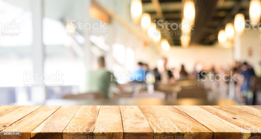 Restaurant Background With People wood table on blurred people in restaurant background stock photo