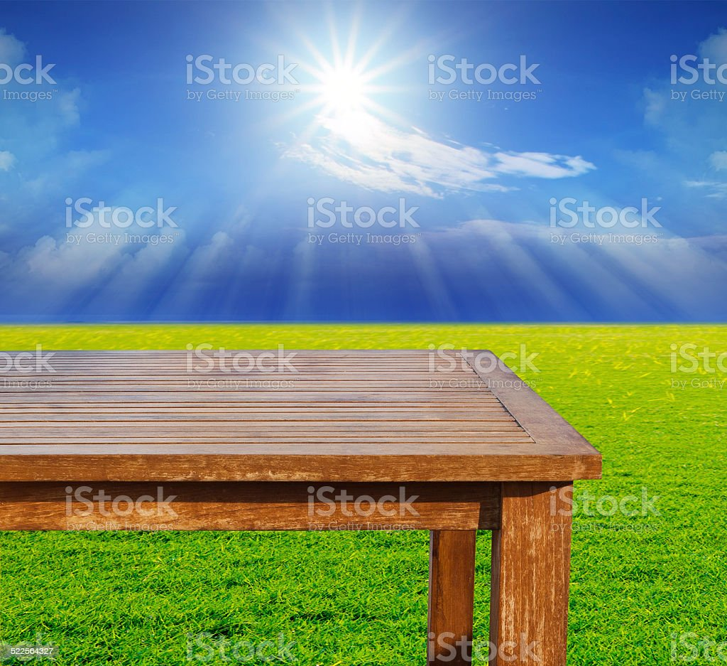 wood table on green field with shining sun on blue sky stock photo