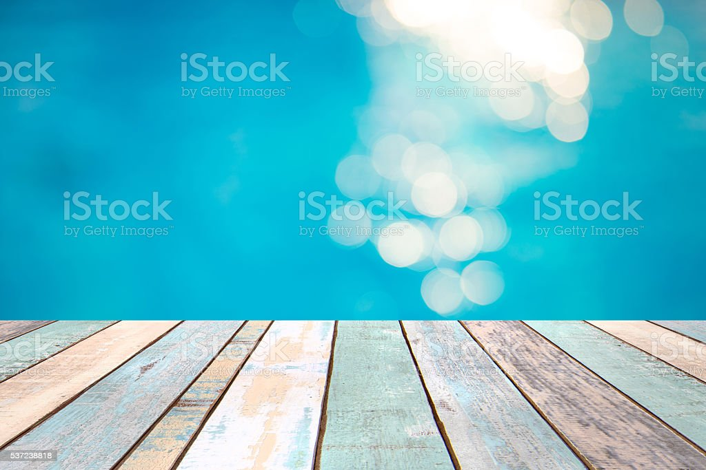 Wood table top and blurry blue water bokeh abstract background stock photo