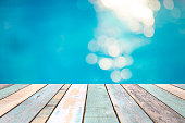 Wood table top and blurry blue water bokeh abstract background