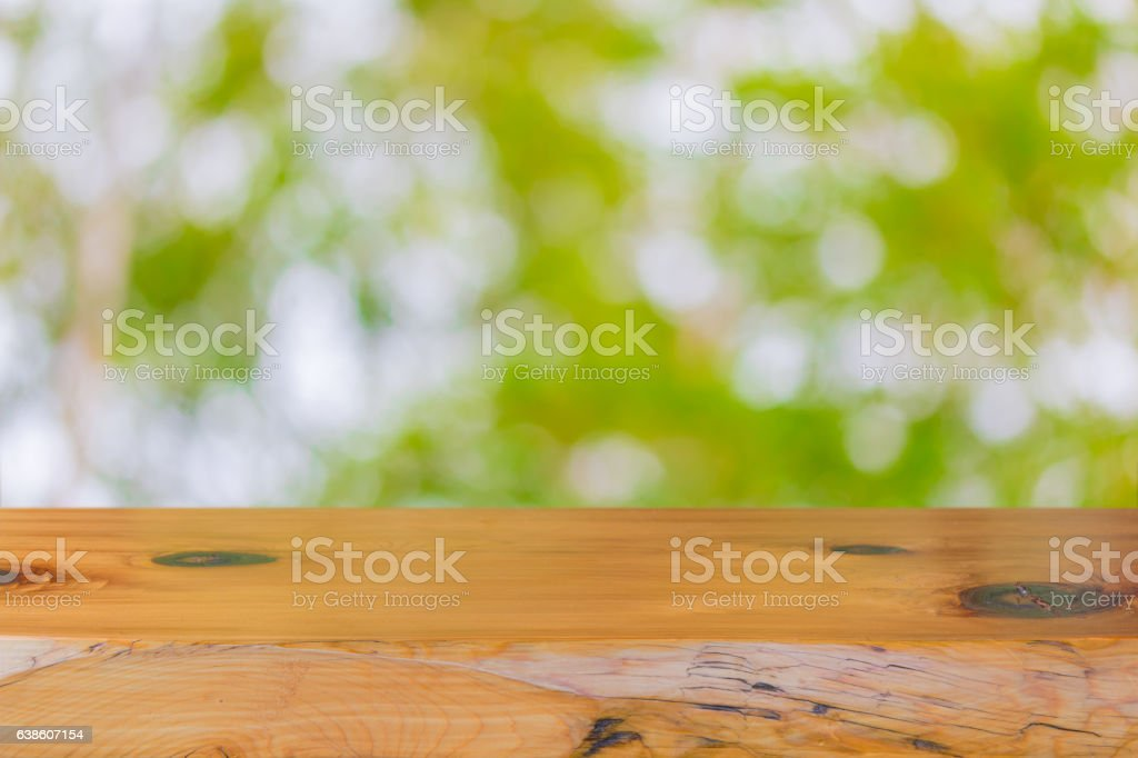 Wood table top on abstract green background. stock photo