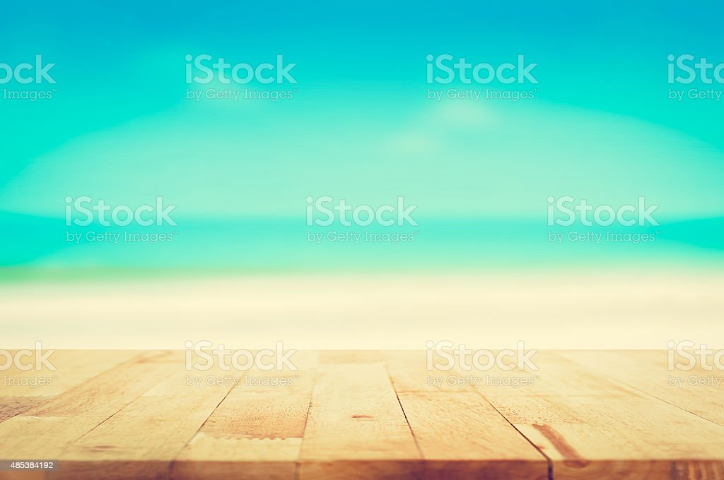 Wood table top on blurred beach background, vintage tone stock photo