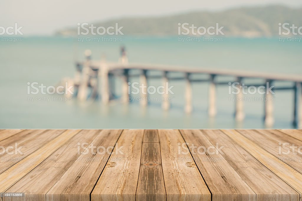 Wood table top on blurred blue sea and beach background, stock photo