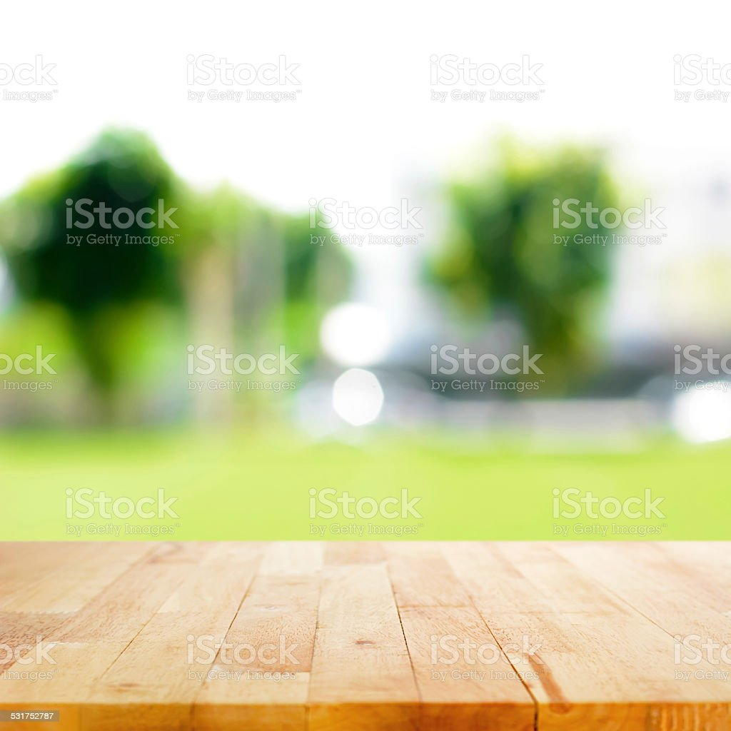 Wood table top on blurred green nature abstract background stock photo