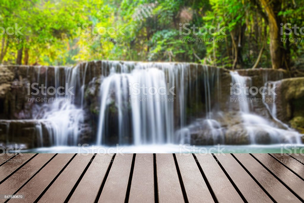 Wood table top on blurred waterfall tropical deep forest stock photo