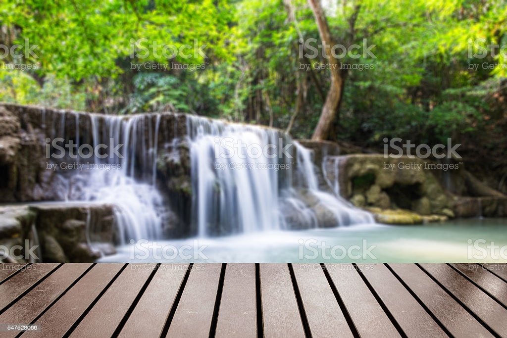 Wood table top on blurred waterfall tropical rain forest stock photo