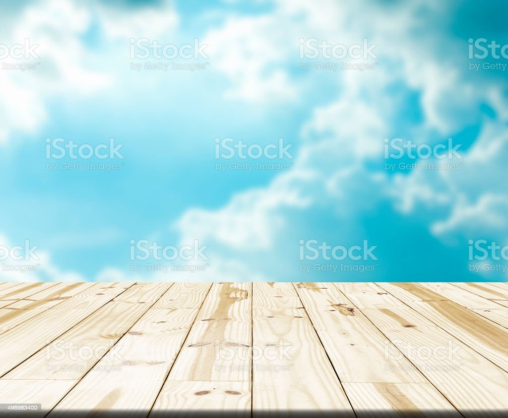 Wood table top on blurry blue sky in background royalty-free stock photo