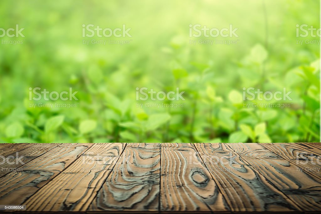 Wood table top on blurry green abstract background stock photo
