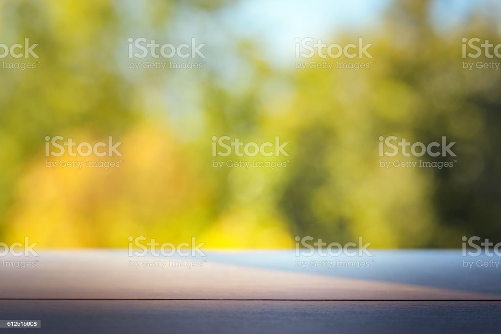Wood table top on colorful blurred abstract outdoor background. stock photo