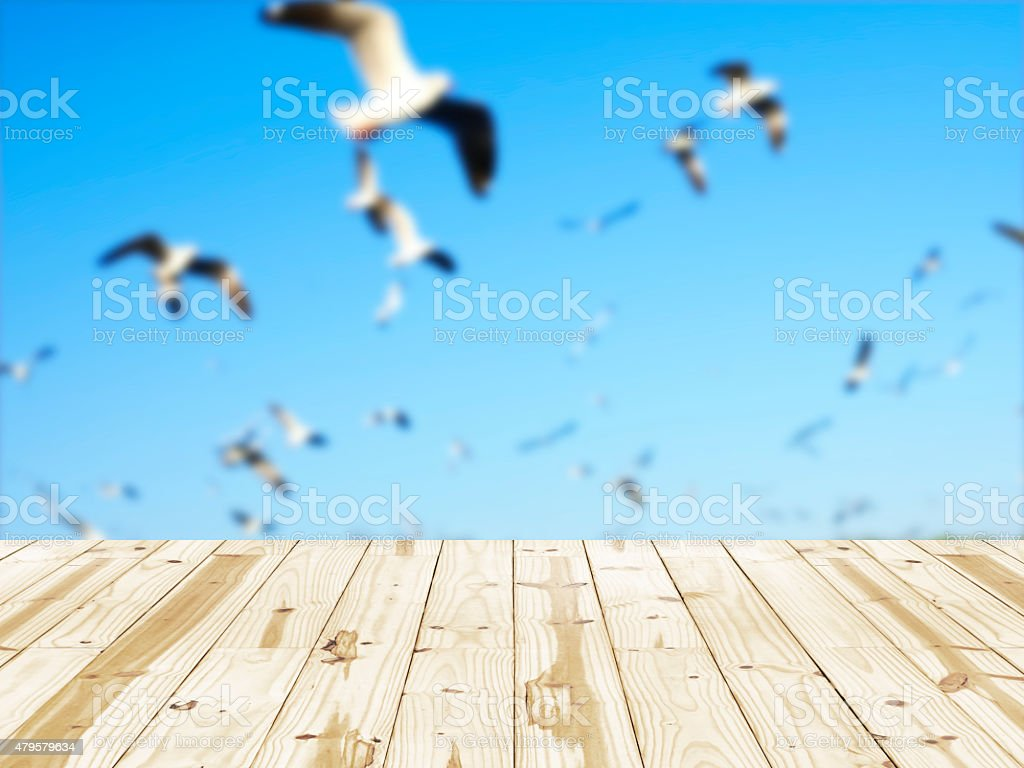Wood table top on flying birds blurry backgrounds. royalty-free stock photo