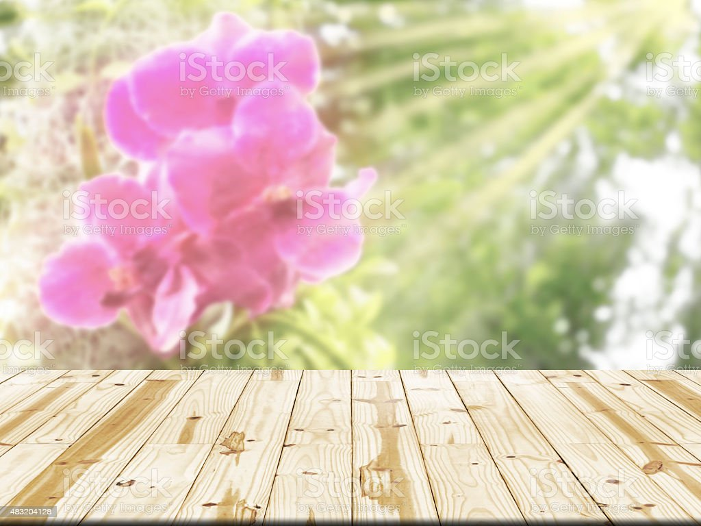 Wood table top on orchid flowers with sunrays blurred background royalty-free stock photo