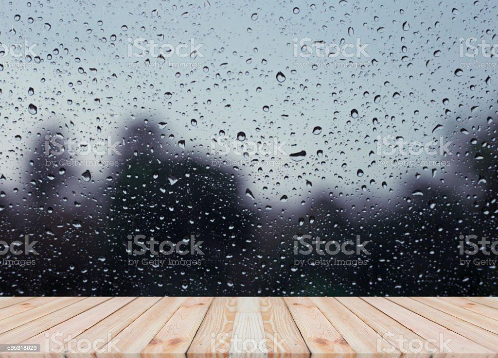 Wood table top on rain drops on clear window stock photo