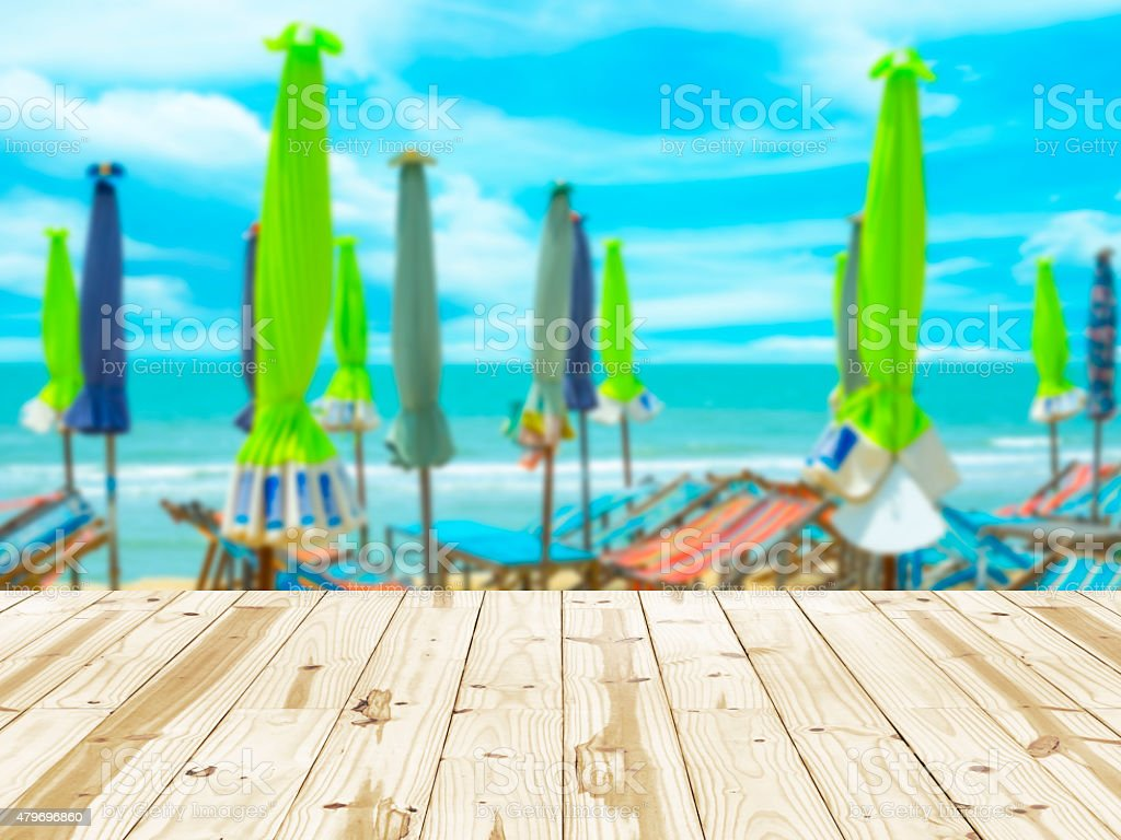Wood table top on sea beach with umbrella blurry backgrounds. royalty-free stock photo