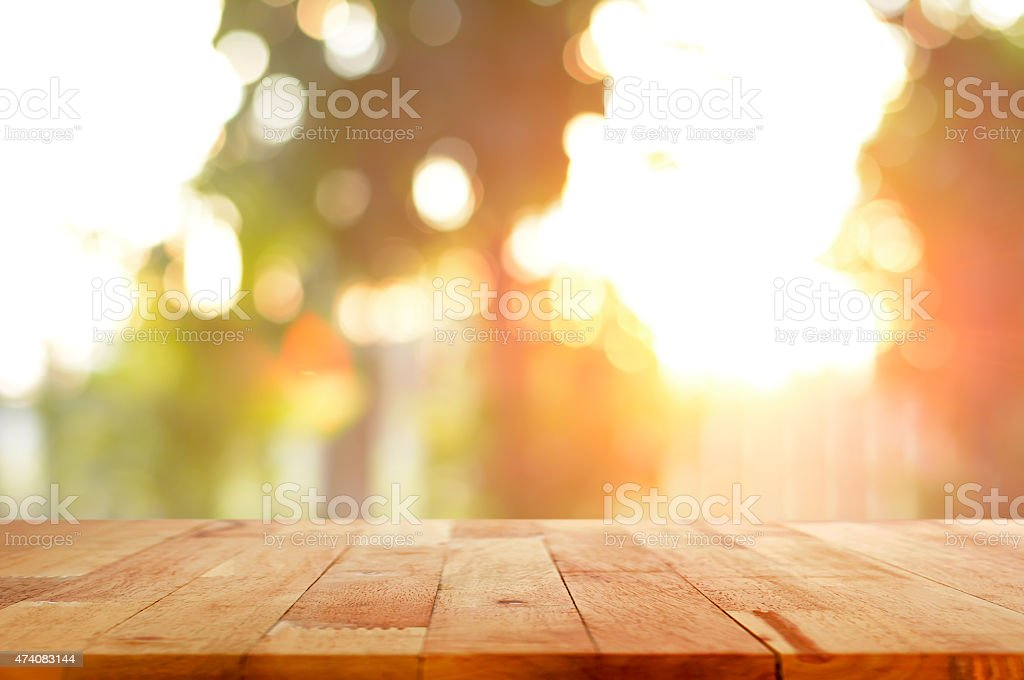 Wood table top on shiny sunlight bokeh background stock photo