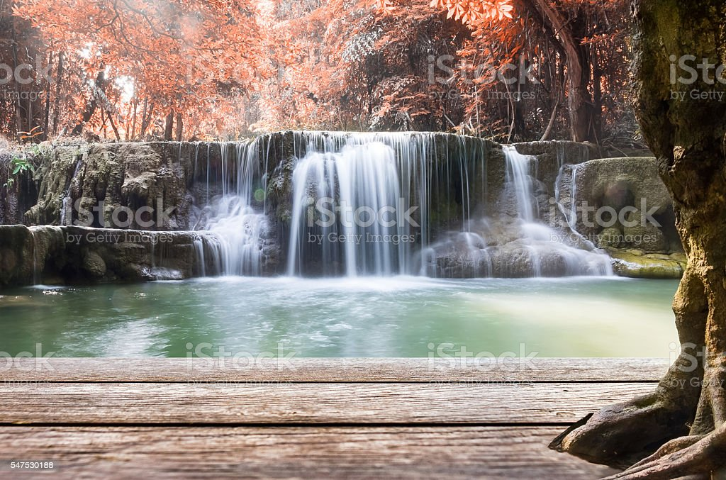 Wood table top on waterfall autumn leaf scene in thailand stock photo