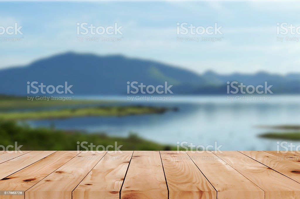 Wood table top perspective on blurred bright landscape stock photo