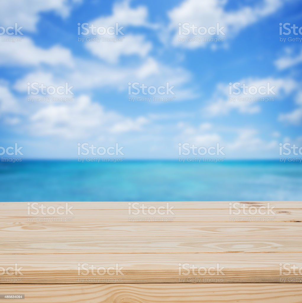 Wood table top with blue sea background stock photo