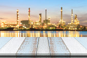 Wood table top with blurred Oil refinery plant at dusk.