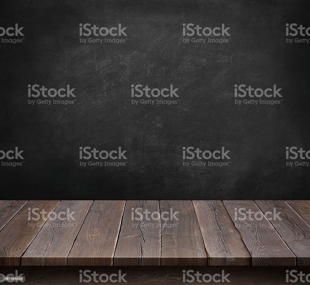 Wood table with blackboard background stock photo