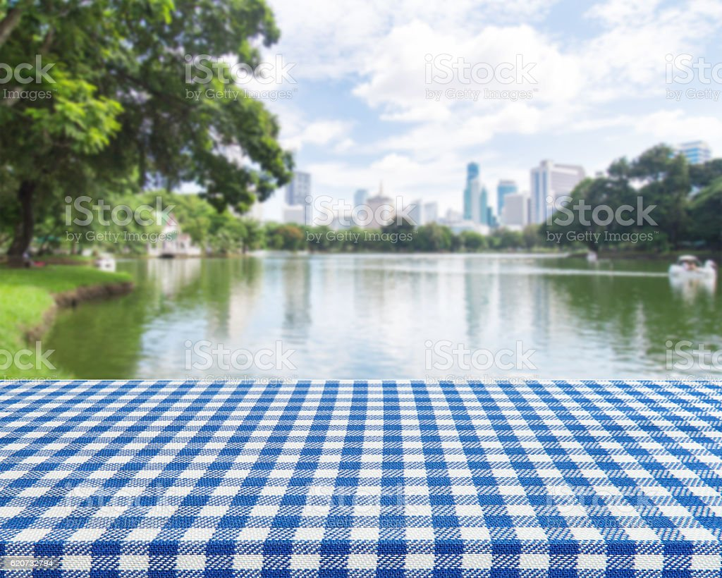 Wood table with blue table cloth on blur park background stock photo