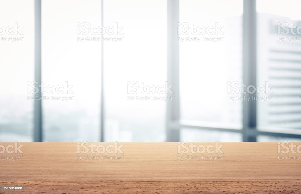 Wood table with blur room office and window city view stock photo