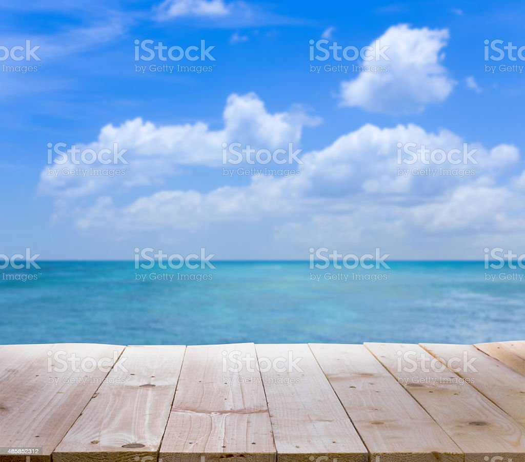 Wood table with blur  seascape and blue sky background stock photo