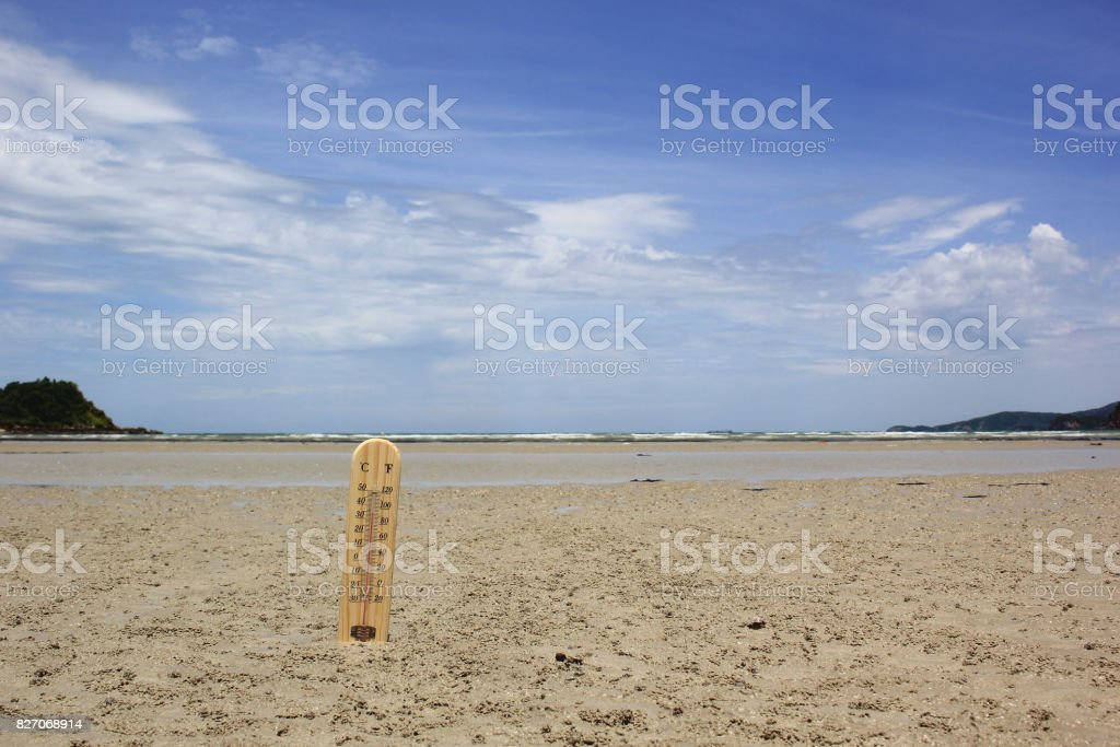 wood thermometer on the sand beach stock photo