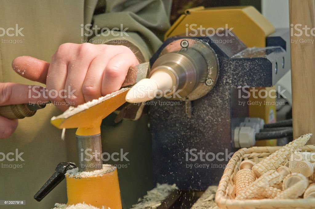 Wood turner manufactures small wood trees at the turning lathe stock photo
