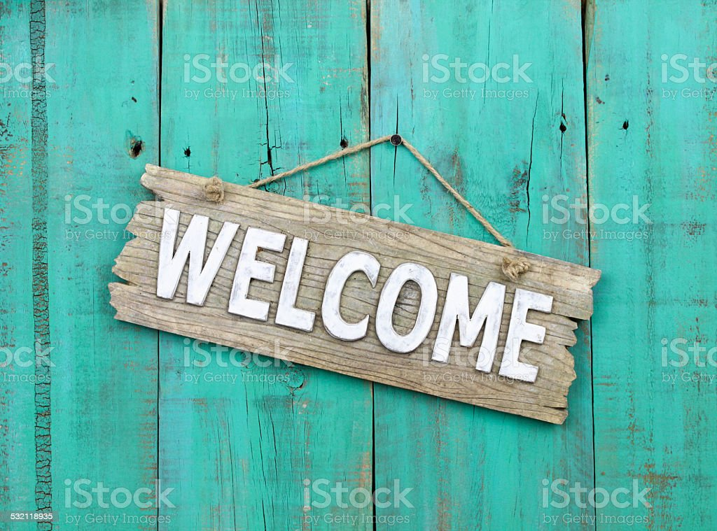 Wood welcome sign hanging on teal blue door stock photo