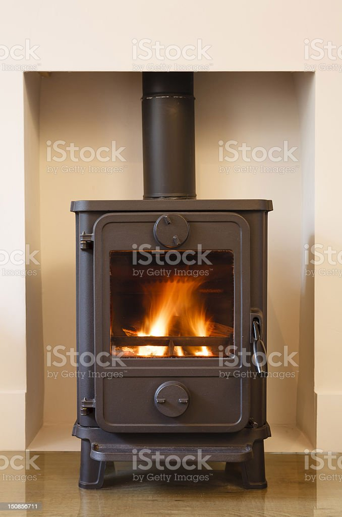 Wood-burning stove against beige wall royalty-free stock photo