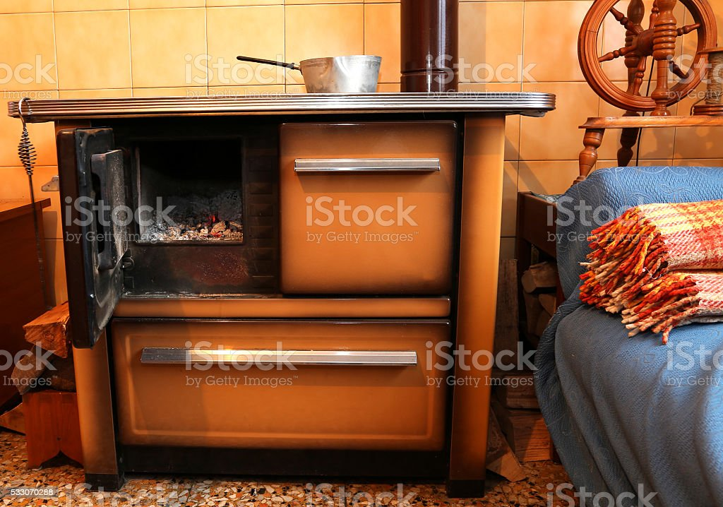 wood-burning stove in the kitchen of ancient home stock photo
