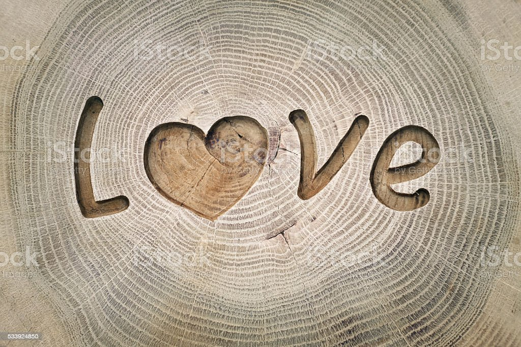 Woodcarving. Inscription Love. heart symbol. Background for your design stock photo