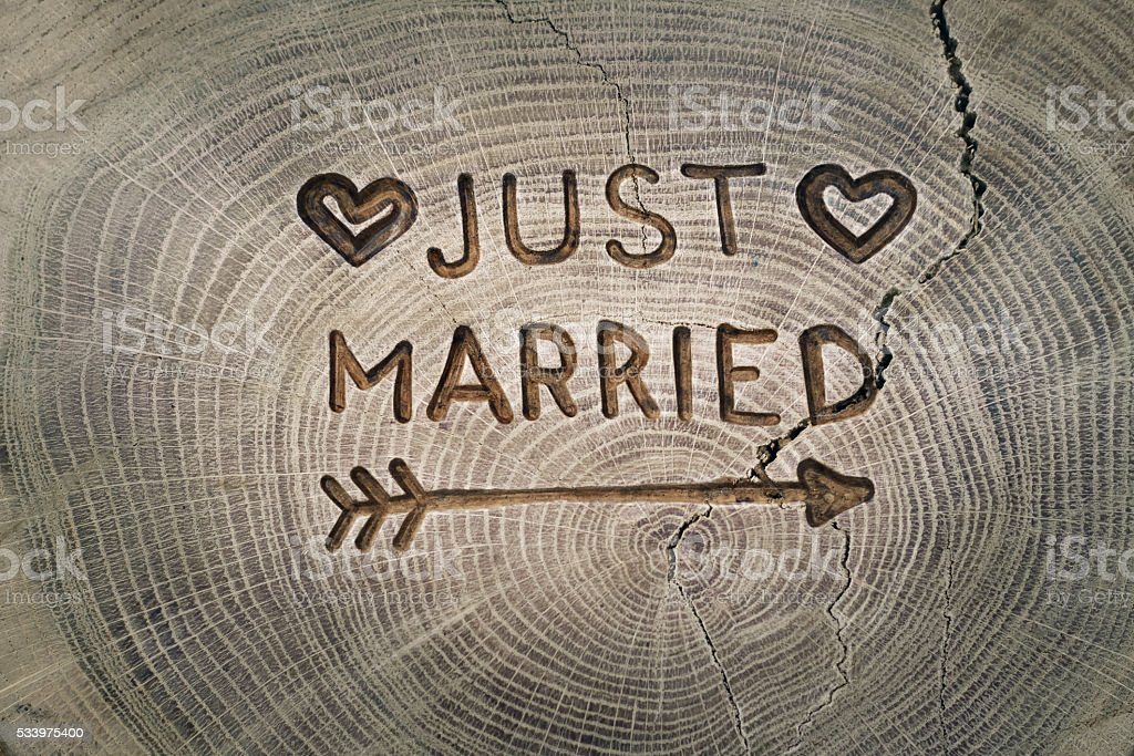 Woodcarving. Newlyweds, Just married, inscription on the wedding. Background stock photo
