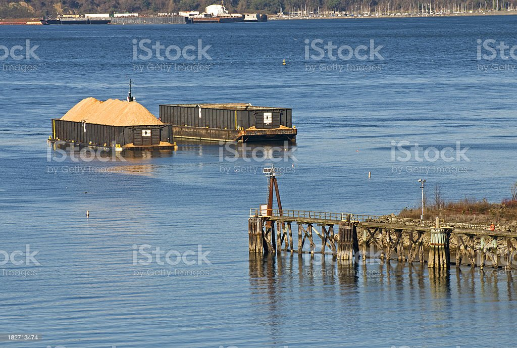 Woodchip barges at pulp mill royalty-free stock photo