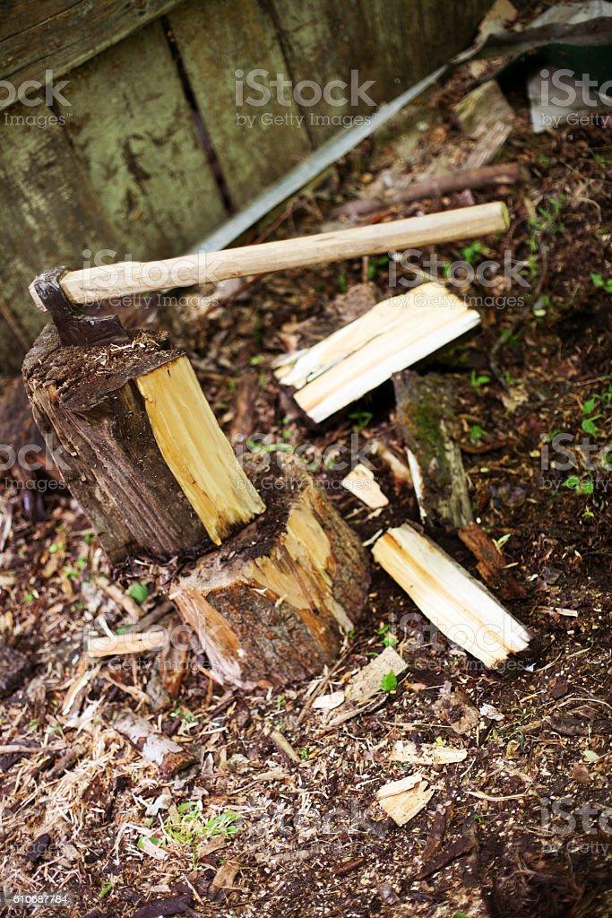 Woodcutting ax stuck in a log. stock photo